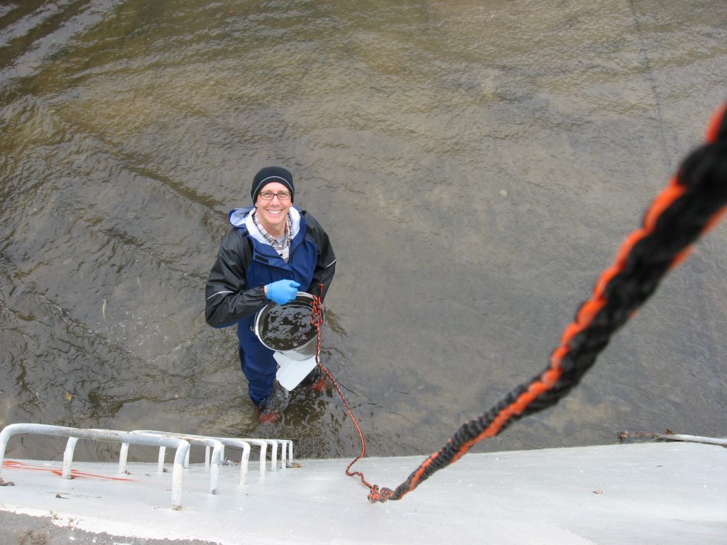 Man sampling water quality with bucket