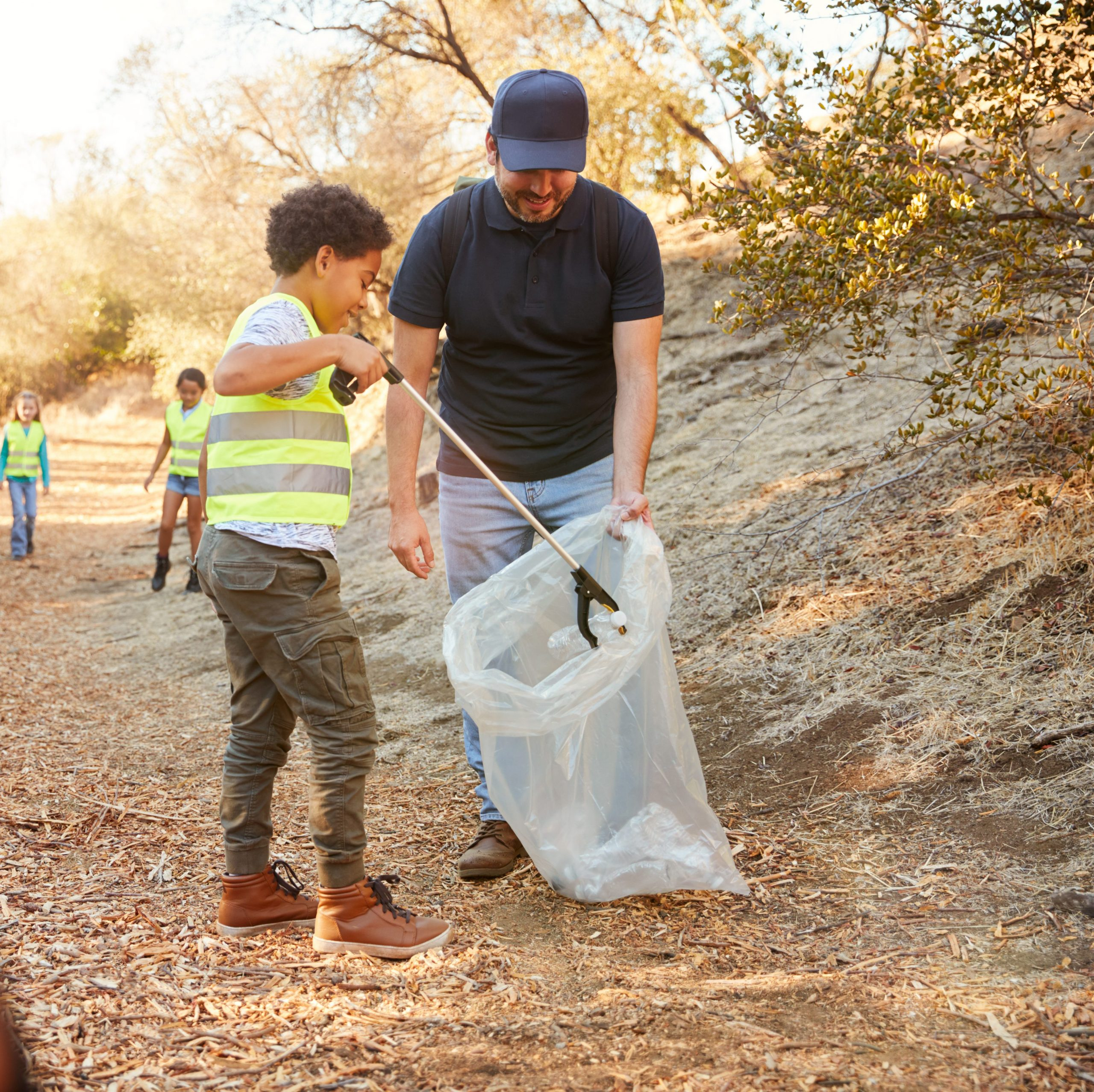 Kid using trash picker up in a community clean up